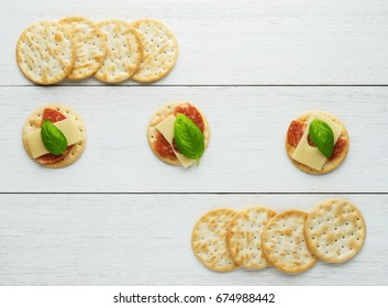 Crackers with cheese and  salami  on vintage wooden background.Snacks - top view