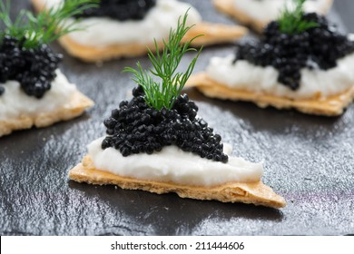 crackers with cream cheese and black caviar, horizontal