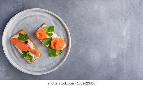 Cracker mit Lachs auf dem Teller. Draufsicht, Kopienraum
