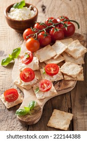 crackers with soft cheese and tomatoes. healthy appetizer