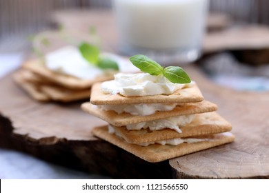 crackers spread with soft cheese with basil leaves.