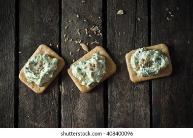 crackers topped with cheese and sesame on wooden background