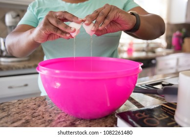 Cracking an egg into a mixing bowl