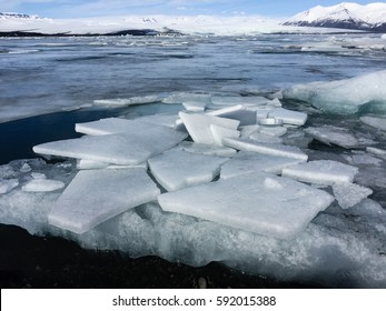 Cracking ice floe floating on turquoise lake, Jokulsarlon Glacier Lagoon, natural phenomenon with snow-capped mountain backdrop on bright blue sky in southeast Iceland.