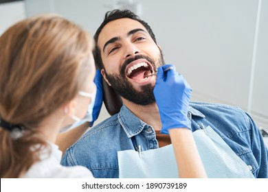 Cracking smile. Handsome caucasian man sitting in armchair at office of dentist while blonde careful female doctor examining his teeth. People, medicine, stomatology and health care concept
