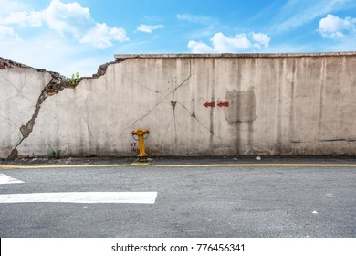 Cracking wall beside the street with blue sky