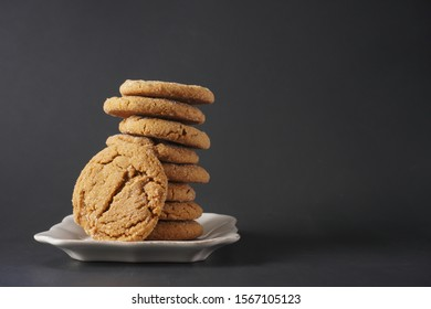 A crackly gingerbread cookie leans against a stack of cookies on a white plate with black background; copy space