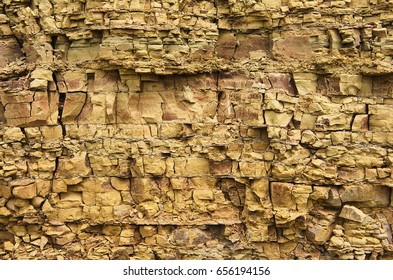 Cracks and colorful layers in natural sandstone as a background. The pattern of the variegated sandstone Geological layers of earth. Sedimentary stone texture closeup. Layers of yellow and brown stone