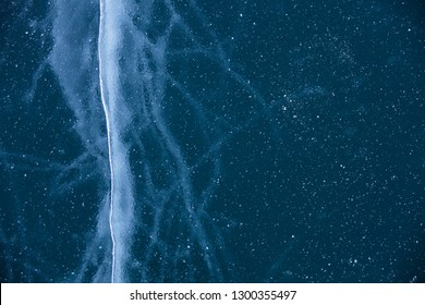 Cracks in ice of Baikal lake. Top view. Winter texture