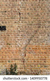 Cracks in an old red brick wall due to subsidence