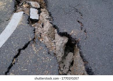 cracks on asphault rural road. damaged collapsed street