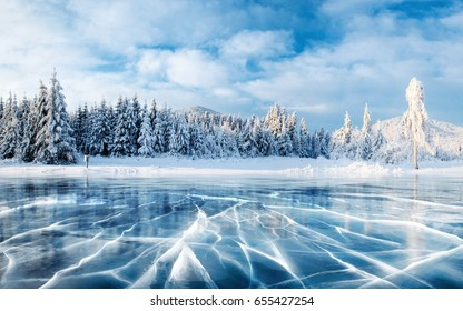 Photo of Cracks on the surface of the blue ice. Frozen lake in winter mountains. It is snowing. The hills of pines. Carpathian Ukraine Europe.