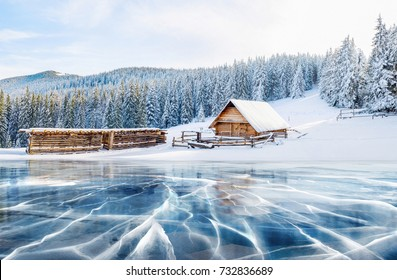 Cracks on the surface of the blue ice. Frozen lake in winter mountains. It is snowing. The hills of pines and cabin in the mountains. Mysterious fog. Carpathians Ukraine