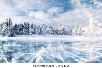 Cracks on the surface of the blue ice. Frozen lake in winter mountains. It is snowing. The hills of pines. Carpathian Ukraine Europe