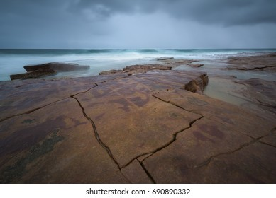 Cracks in the rocks on a rocky beach looking out over the Indian Ocean towards a dramatic storm.