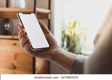 Cracow, Malopolskie / Poland - March 13 2020: Woman hand holding Apple iPhone 11 Pro blank screen on home interior background
