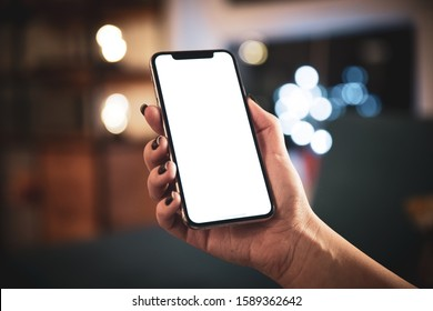 Cracow, Malopolskie / Poland - October 15 2019: Woman hand holding iPhone 11 Pro on bokeh home interior background