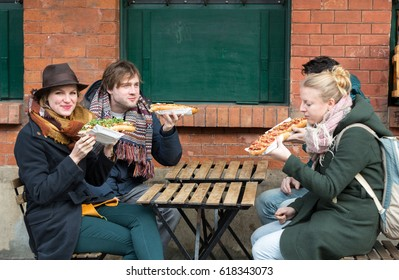 CRACOW, POLAND - JANUARY 30, 2016:  Young people eat Zapiekanka - Polish fast-food a casserole on Plac Nowy in Kazimierz district , Krakow. Poland