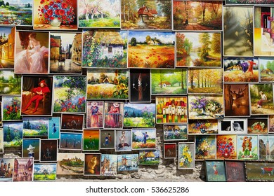 CRACOW, POLAND JULY 13: Display of paintings by local artists on street of the Old Town on July 13, 2014 in Cracow, Poland. Collage of kitschy paintings for sale.