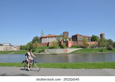 CRACOW, POLAND - JULY 27 - Tourist on bike admiring Royal castle over the Vistula River in on July 27, 2012 in Krakow (Cracow), Poland