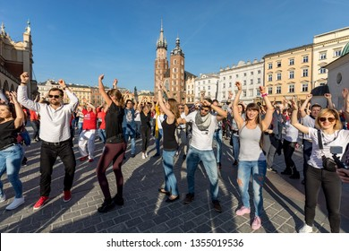 Cracow, Poland - Maerch 30, 2019:  International Flashmob Day of Rueda de Casino. Several hundred persons dance Hispanic rhythms on the Main Square in Cracow. Poland