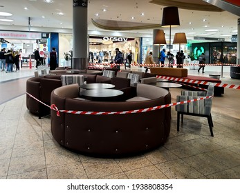 """Cracow, Poland-Feb 2021: View on a fenced with warning tape cafe closed during lockdown of gastronomy in the shopping mall """"Galeria Krakowska"""" during pandemic of coronavirus. Selected focus."""