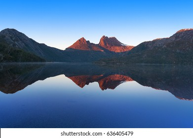 Cradle Mountain landscape perfectly reflected in mirror like water surface of lake Dove. Cradle Mountain National Park, Tasmania, Australia