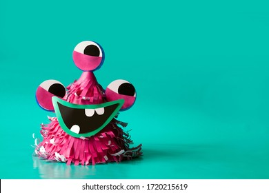 Craft alien from pink paper on a blue background. Children's art.  Made from reusable materials such as paper, cardboard and plastic covers.