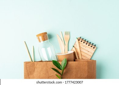 Craft bag, glass jar, green leaves and recycled tableware top view. Flat lay Zero waste, eco friendly, natural organic plastic free concept. Cutlery, earth, biodegradable with copy space.