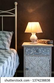 Craft bedside lamp on a bedside table in bedroom. Cozy bedroom interior.