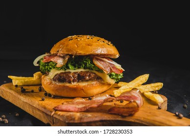 Craft beef burger with bacon and french fries on wooden table isolated on black background.
