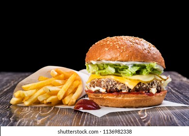 Craft beef burger and french fries on wooden table