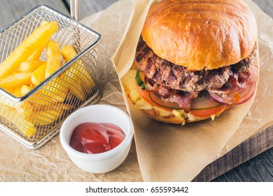 Craft beef burger and french fries with sauce on wooden table