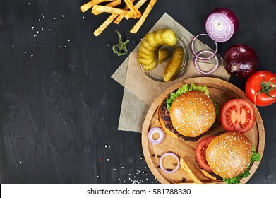 Craft beef burgers on round wooden cutting board with vegetables and french fries. Flat lay on black textured background.