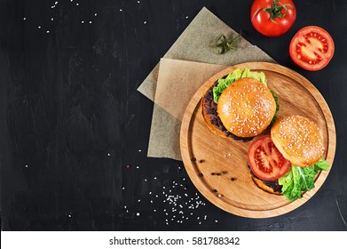 Craft beef burgers on round wooden cutting board with vegetables. Flat lay on black textured background.
