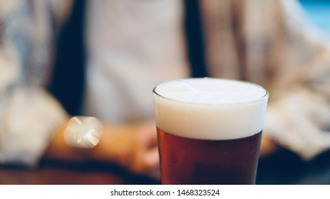craft beer with foam and blurred man as background, international beer day concept