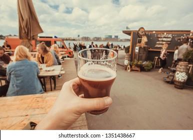Craft beer glass in drinker hand on street food market of Copenhagen, Denmark. Leisure in Scandinavia with drinks and food of popular city market.