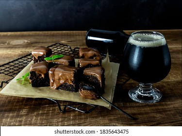 Craft beer imperial stout with sweet chocolate brownies on the wooden table.