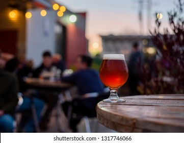 craft beer on the patio, patio table with beer, patio lights, microbrewery, people in the background