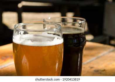craft beer on wooden table outdoors, 1 glass of lager or lager and a glass of stout or porter - Shutterstock ID 1920413819