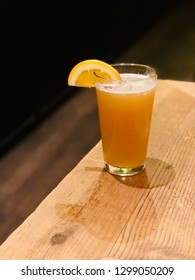 Craft Beer in Pint Glass with Orange Fruit Slice on Wooden Table