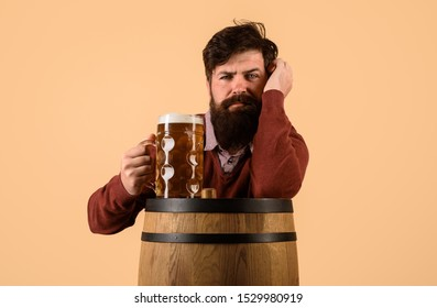 Craft beer at restaurant. Oktoberfest. Serious man with wooden barrel of beer and mug of beer. Brewer. Holliday, drinks, alcohol, leisure concept. Bearded man hold glass and barrel with craft beer.