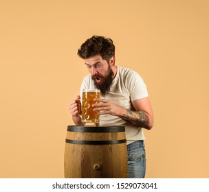 Craft beer at restaurant. Surprised man with wooden barrel of beer and mug of beer. Brewer. Oktoberfest. Holliday, drinks, alcohol, leisure concept. Bearded man hold glass and barrel with craft beer.