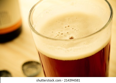 Craft Beer - This is a shot of a cold glass of beer shot at a high angle in a warm, retro color tone. Shot with a shallow depth of field.