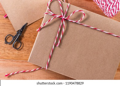 craft box tied with red and white rope on wooden table