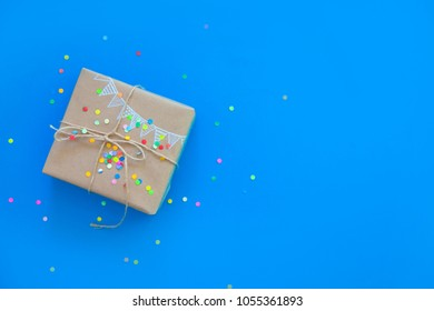 Craft broun gift box. Drawing of a colored garland, flags. Blue and turquoise background. Confetti.