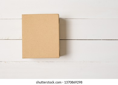 Craft brown square gift box on a light wooden background. Flat lay.