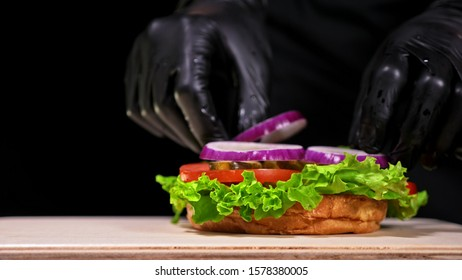 Craft burger is cooking on black background in black food gloves. Consist: red sauce salsa, lettuce, red onion, pickle, cheese, chilli green pepper, air bun and marbled meat beef. Not made ideal