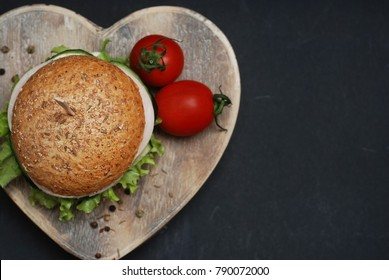 Craft Burgers with Vegetables and Chiken on Heart Shape Wooden plate. Love for Hamburgers Concept. Flat lay on Black background with Tomatoes.