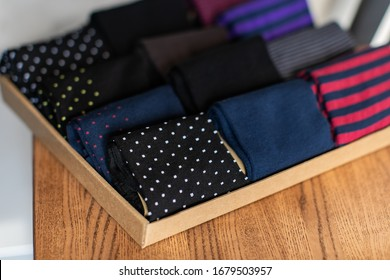 Craft cardboard box with a set of colorful men's socks on wooden surfaces under a sunlight